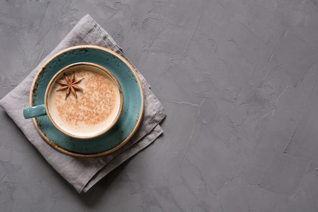 Té o café indio masala en taza azul con especias y canela en negro. vista superior.