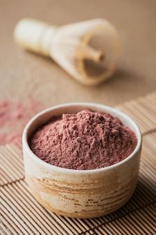 Té en polvo de color orgánico matcha con batidor de bambú de herramientas japonesas sobre superficie beige