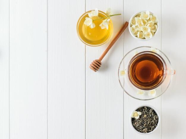 Té recién preparado con flores de jazmín y miel sobre una mesa de madera blanca