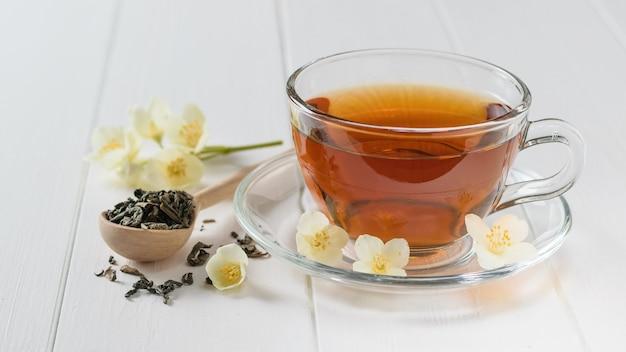Té recién preparado con flores de jazmín en una rústica mesa blanca.