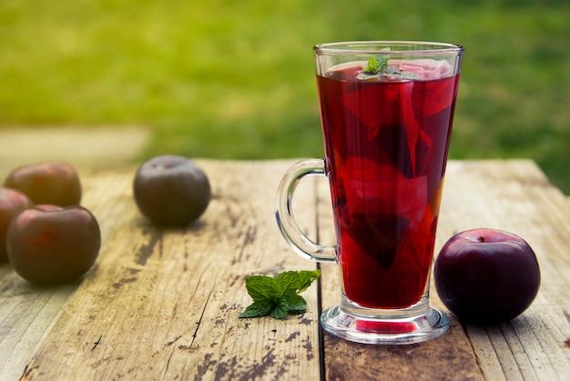 Té rojo de la fruta herbaria en la taza de cristal con las ciruelas en la tabla de madera.