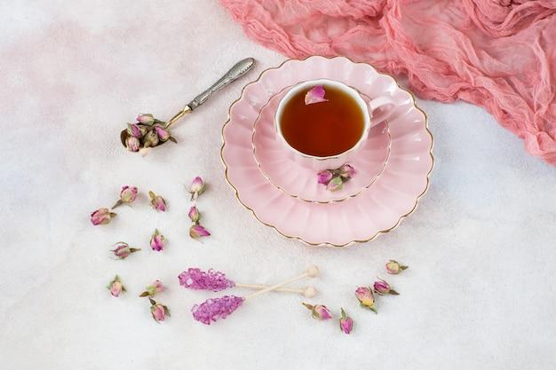 Té de rosas en una taza rosa, capullos de rosa, una cuchara vieja y azúcar rosa