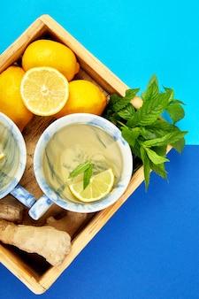 Té saludable dos tazas con limón, jengibre, menta