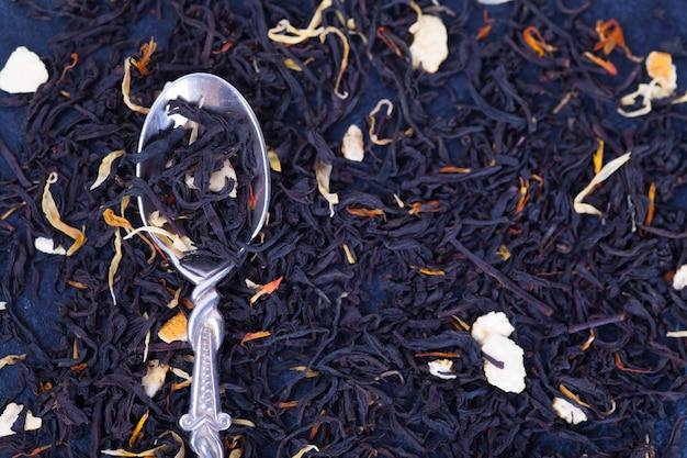 Té seco con pétalos de frutas y flores y una cuchara de plata como fondo
