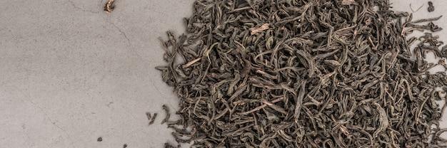 El té seco se vierte disperso sobre un fondo gris con textura.
