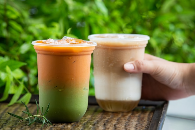 Té tailandés helado mezclado con té verde sobre superficie de madera