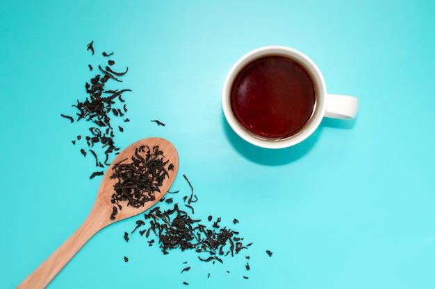 Té en una taza blanca, una cuchara de madera, esparcido con té de hojas a medio pecho sobre un azul turquesa