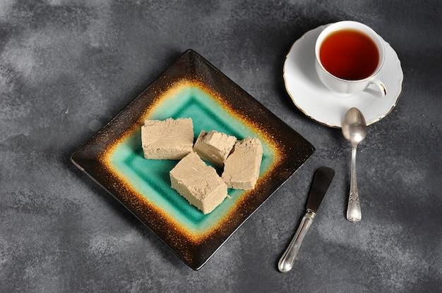Té en una taza con un borde dorado y un platillo y una halva cortada en trozos