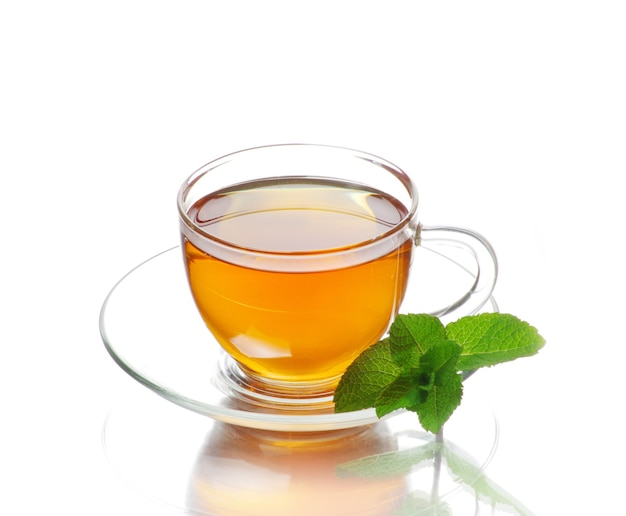 Té en taza con hojas de menta y limón aislado sobre fondo blanco.