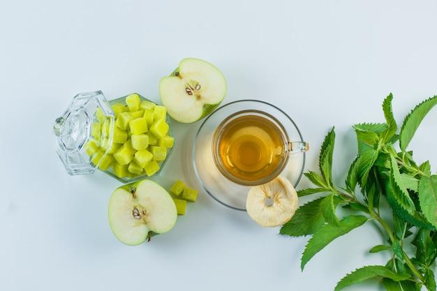 Té en una taza con manzana, frutos secos, terrones de azúcar, hierbas planas yacen sobre un fondo blanco.