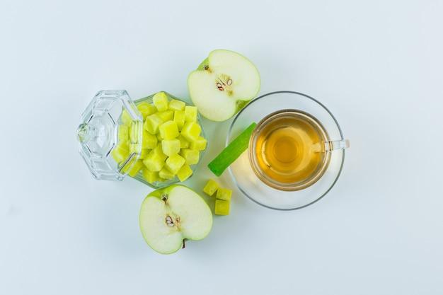 Té en una taza con manzana, terrones de azúcar, caramelo plano yacía sobre un fondo blanco.