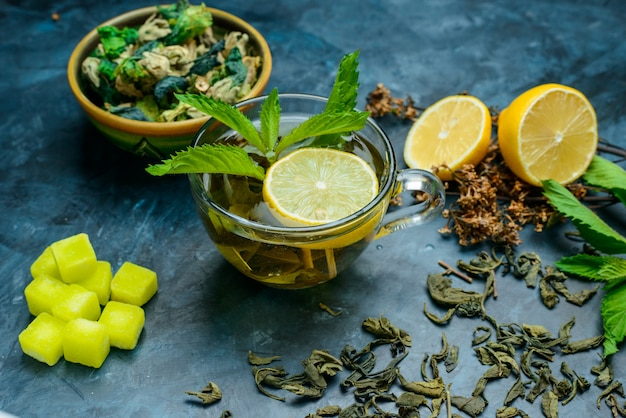 Té en una taza con menta, hierbas secas, limón, terrones de azúcar vista de ángulo alto sobre una superficie azul