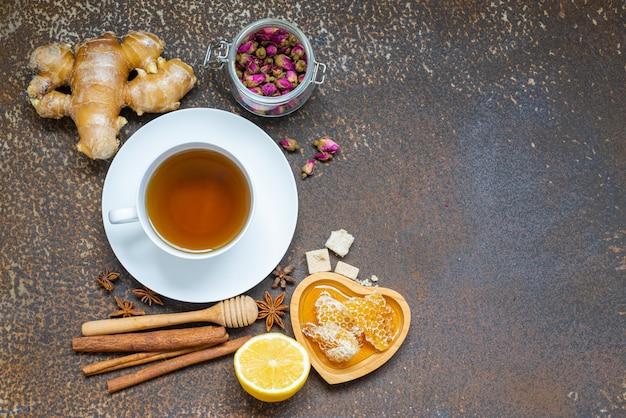 Té, taza de té, hojas de té secas con tetera y hierba, miel, jengibre sobre fondo sucio grunge