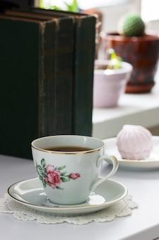 Té en una taza vintage, malvaviscos en un platillo vintage y libros antiguos sobre un fondo claro.