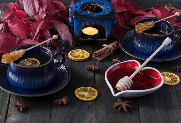 Té en tazas azules con una rodaja de limón, azúcar moreno, miel, decoración, una vela en un candelabro