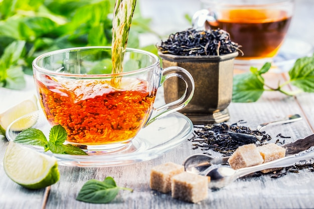 Té. té de menta. té de hierbas. hoja de menta. hojas de menta. té en una taza de vidrio, hojas de menta, té seco, rodajas de limón. té de hierbas y hojas de menta en una placa de pizarra en un restaurante o salón de té.