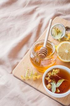 Té con tilo, miel y limón. la bandeja sobre la cama, el concepto del tratamiento de los resfriados.
