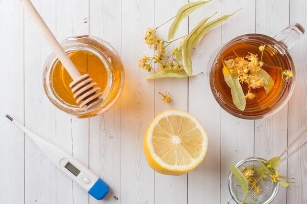 Té con tilo, miel y limón. comida sana, tratamiento de resfriados termómetro sobre la mesa.