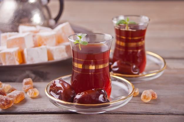 Té turco en copas de cristal tradicionales en la mesa de madera