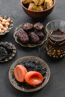 Té turco con dátiles y albaricoque seco; pasas en un plato de hierro arabe para el ramadán