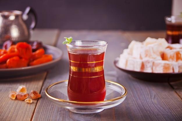 Té turco en tazas de vidrio tradicionales en la mesa de madera