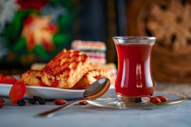 Té turco en vaso tradicional con dulces, frutas secas y nueces para la hora del té