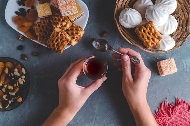 Té turco en vaso tradicional con dulces, frutos secos y nueces para la hora del té. vista superior