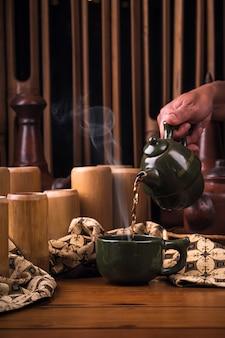 Té verde caliente sobre la olla con vaso