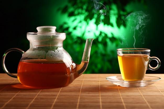 Té verde caliente en tetera de vidrio y taza