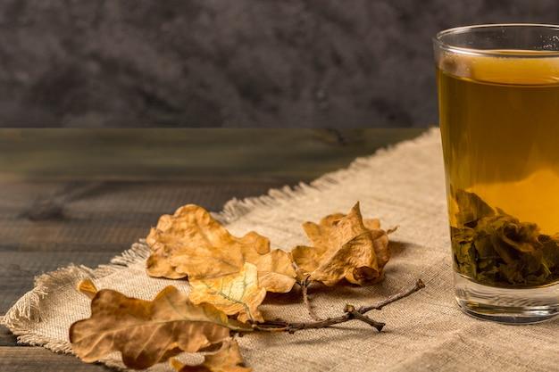Té verde caliente en un vaso y hojas de otoño. té antioxidante y eliminador de toxinas después del spa,