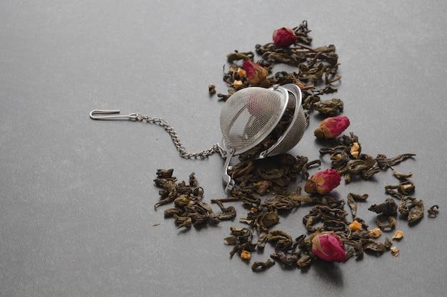 Té verde derramado con una rosa y un colador