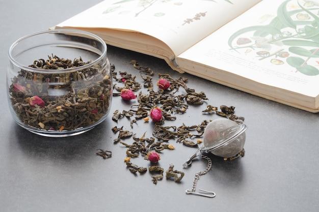 Té verde derramado con una rosa en la mesa de piedra