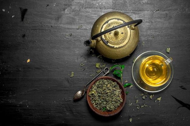Té verde fragante con hojas en la pizarra negra