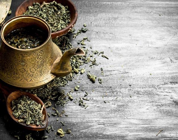 Té verde fragante en una vieja tetera en la pizarra negra