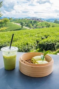 Té verde helado matcha en vidrio transparente de plástico y mesa de pan al vapor con fondo de plantación de té