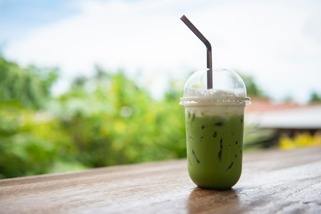 Té verde helado en taza de plástico / matcha té verde latte frappe y paja en mesa de madera con la naturaleza