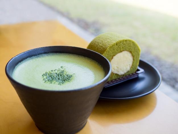 Té verde matcha latte caliente y pastel de rollo de té verde en la mesa de madera
