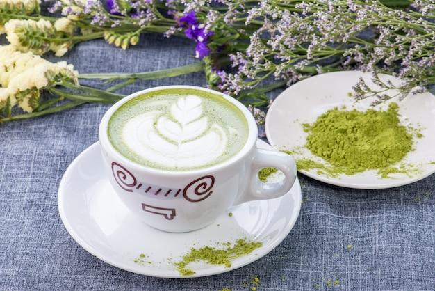 Té verde / matcha latte en una taza con polvo de matcha sobre la mesa