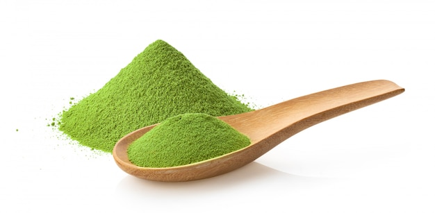 Té verde matcha en polvo en una cuchara de madera en blanco