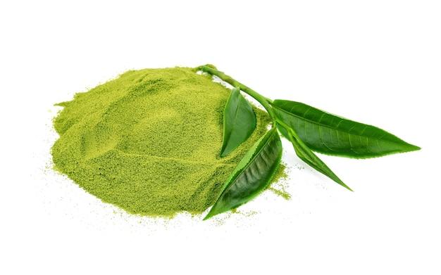 Té verde en polvo y hojas de té verde sobre fondo blanco.