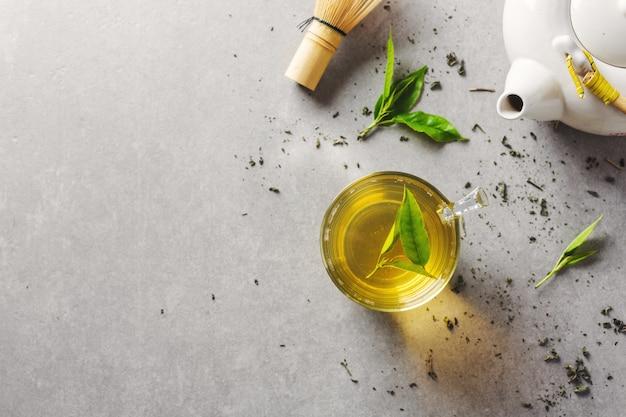 Té verde preparado en taza con hojas de té en la mesa. de cerca.