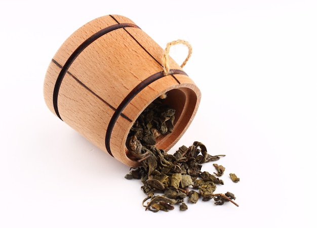 El té verde se seca en un barril sobre una superficie blanca.