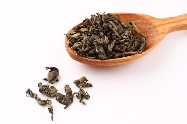 El té verde se seca en una cuchara sobre una superficie blanca.