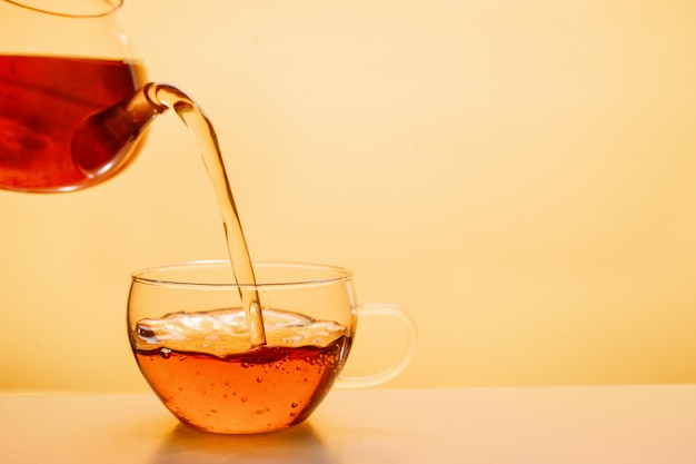 Té se vierte en una taza de té de vidrio