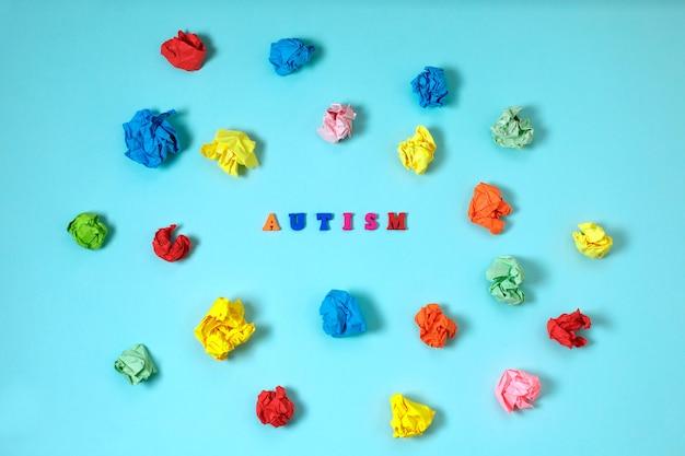 Tea, concepto de autismo con letras y papel arrugado sobre fondo azul