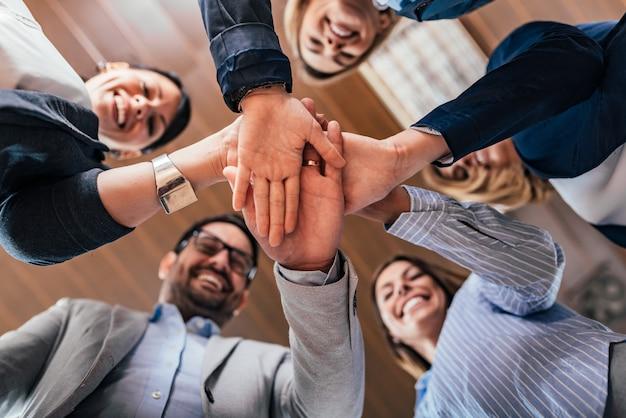 Team building, asociación, concepto de éxito empresarial. vista inferior de los hombres de negocios que ponen las manos juntas.