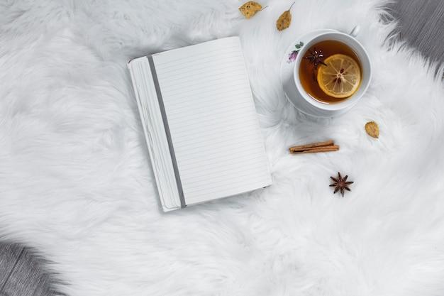 Teatime con cuaderno sobre alfombra blanca.
