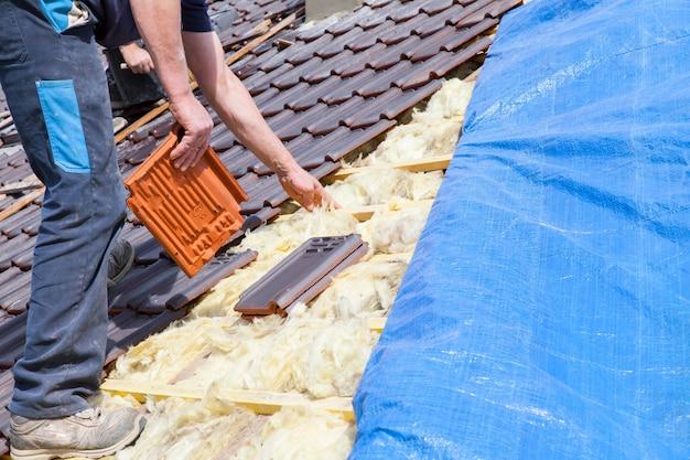 Un techador colocando tejas en el techo