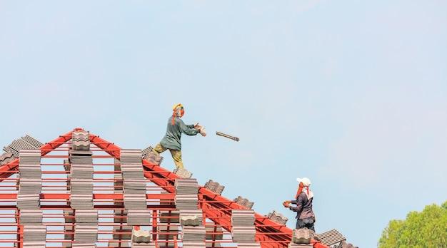 Techador de construcción instalando tejas en el sitio de construcción de viviendas