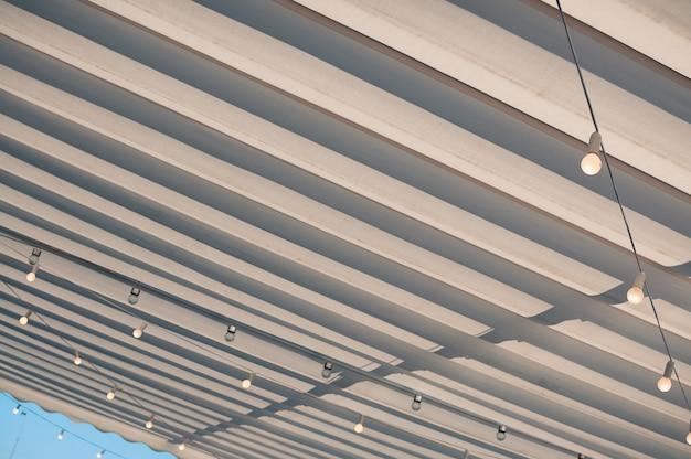 Techo blanco de una terraza, con bombillas colgando debajo del toldo, contra el cielo azul